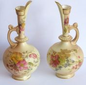 An opposing pair of early 20th century Royal Worcester blush porcelain ewers; each delicately hand