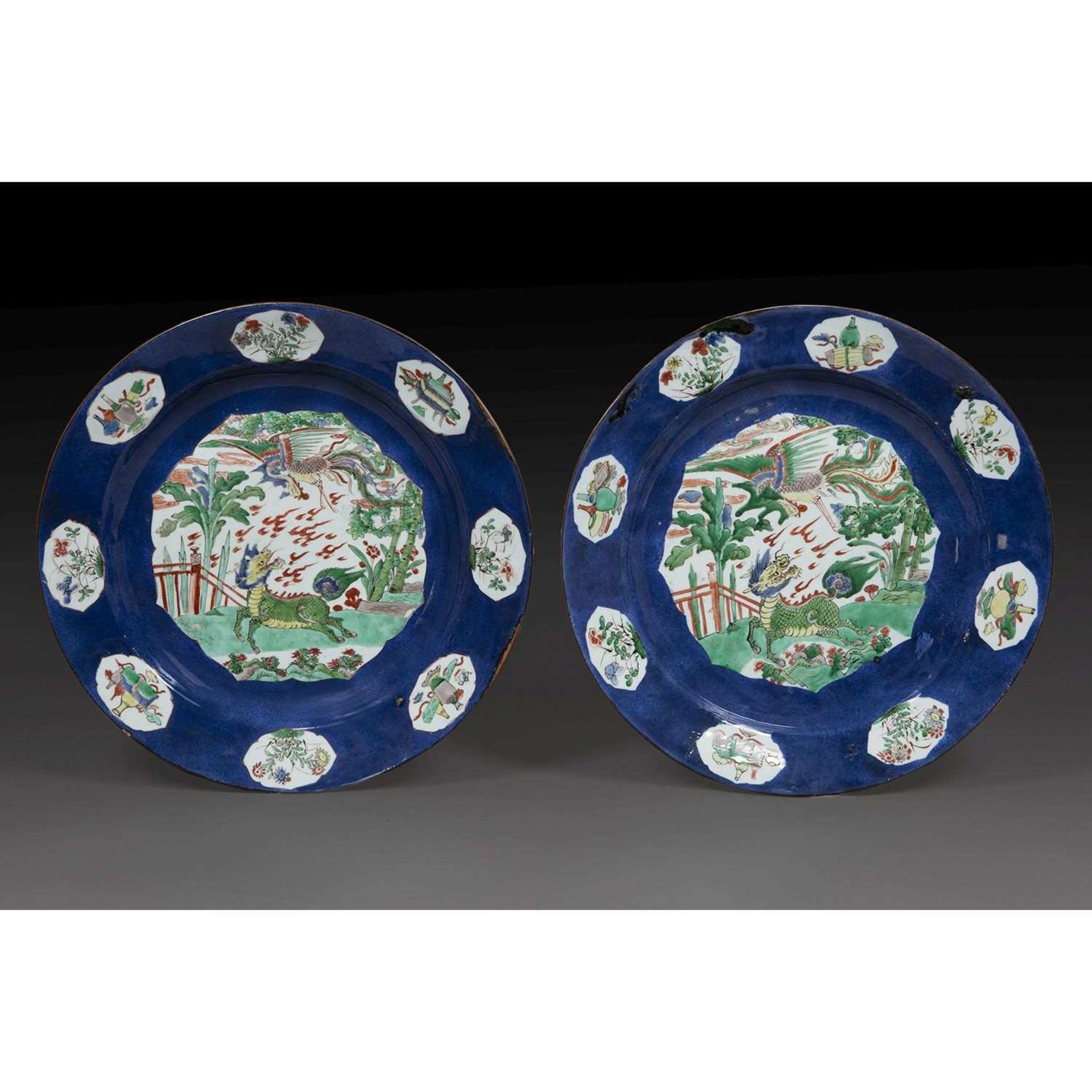 PAIRE DE GRANDS PLATS RONDS en porcelaine et émaux polychromes de la famille verte sur fond bleu