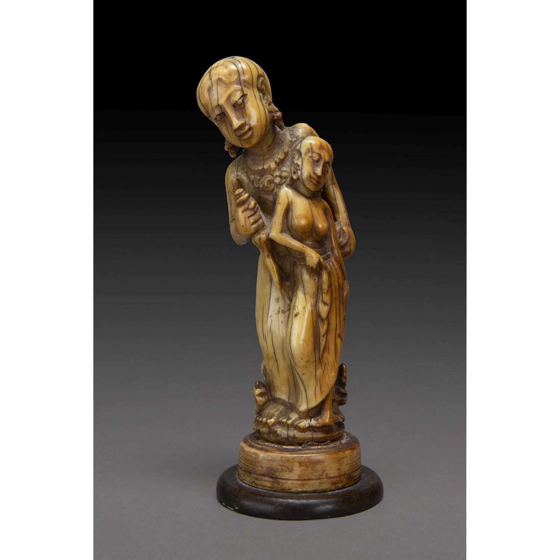 ~ STATUETTE INDIENNE en ivoire sculpté de belle patine, figurant une femme torse nu s'appuyant