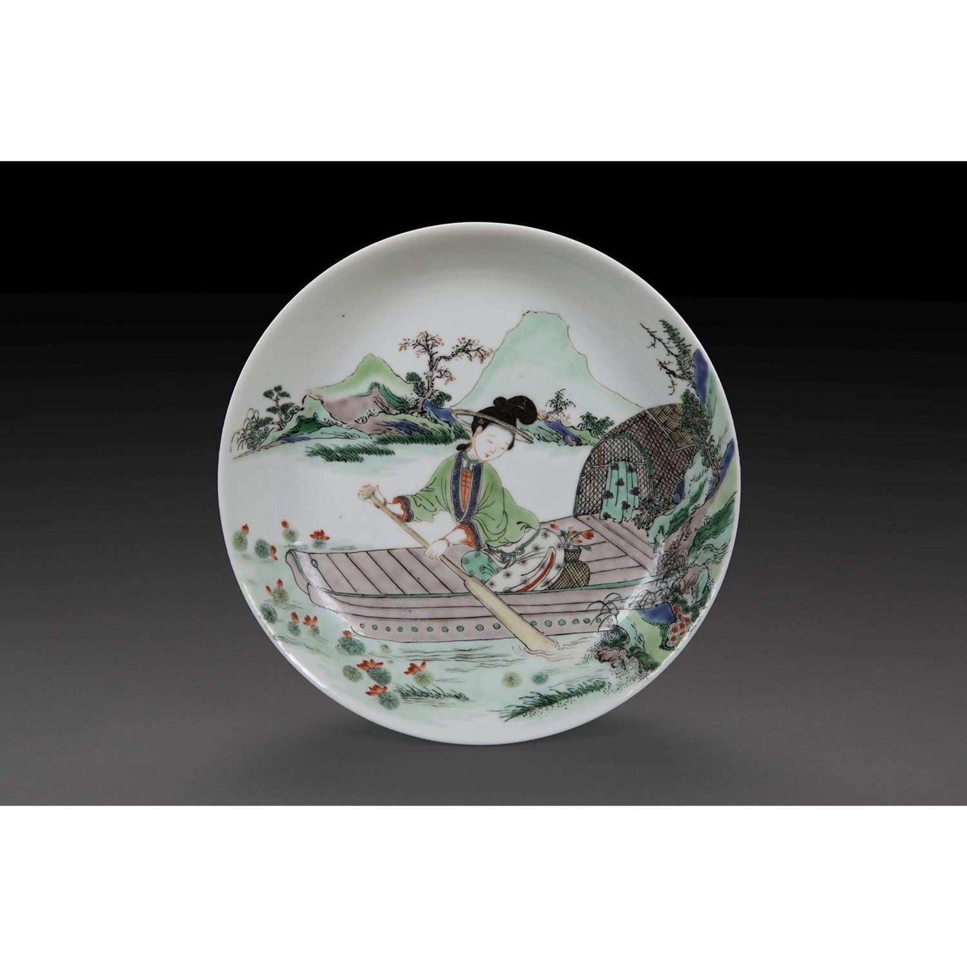 PETIT PLAT CREUX en porcelaine et émaux polychromes de la famille verte, à décor d'une jeune femme