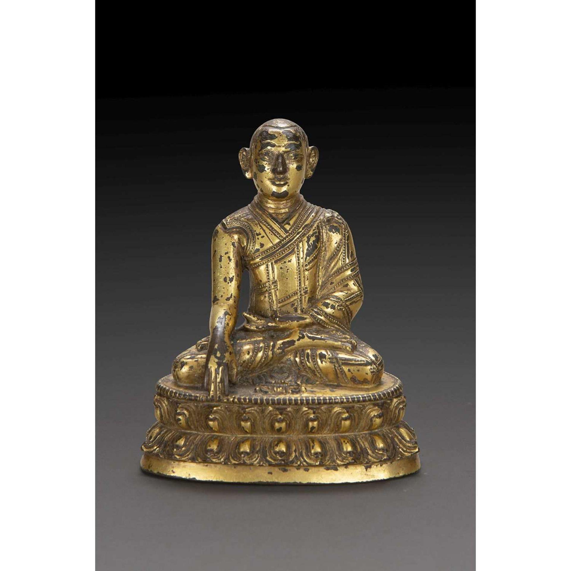STATUETTE DE MOINE en bronze doré, représenté assis sur un socle lotiforme, les mains en