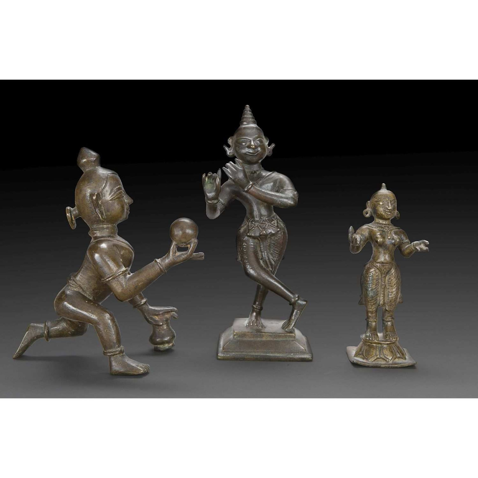 LOT DE TROIS STATUETTES en bronze de patine brune, deux représentant Krishna, jouant de la flûte
