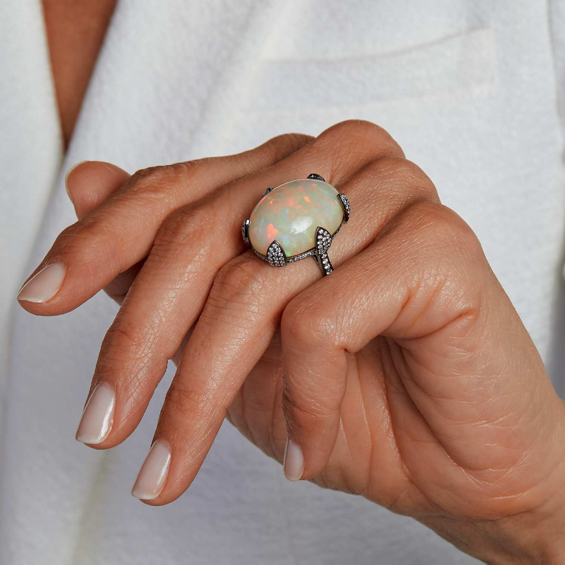 TRAVAIL FRANÇAIS GRANDE BAGUE OPALE Le cabochon d'opale est retenu par des griffes pavées de