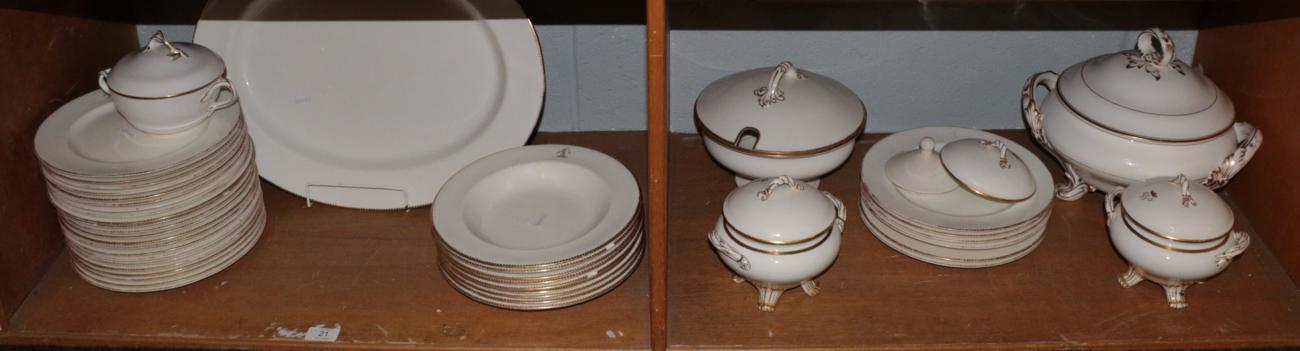 Lot 21 - A group of dinner wares bearing various crests and with gilt borders including tureens; dinner
