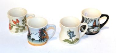 Four Moorcroft mugs (4). One with 1987-2007 on the side of the mug with factory and bottle. All