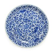 A Chinese Porcelain Saucer Dish, Kangxi, painted in underglaze blue with lotus and other flowers,