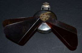 A White Metal Mechanical Fan, with tortoiseshell blades, a central brass metal ring stamped ''