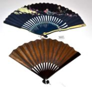 A Striking Fan, the wood sticks painted black, serpentine, the guards of shaped bone. The fan,