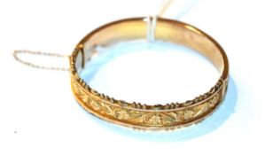 A 9 carat gold hinged bangle . Gross weight 12.3 grams.