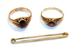 Two 9 carat gold garnet rings, finger sizes R and S and a 9 carat gold bar brooch . Larger garnet