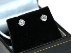 A pair of diamond solitaire earrings, the round brilliant cut diamonds in white four claw
