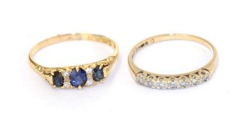 An 18 carat gold synthetic sapphire and diamond ring, three graduated oval sapphires spaced by trios