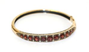 A 9 carat gold garnet and diamond hinged bangle, the eleven graduated garnets with eight-cut diamond
