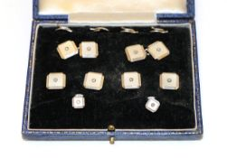 A cased Art Deco mother-of-pearl and diamond dress stud and cufflink suite, comprising four buttons,