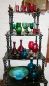 A collection of cranberry wine glasses, green glasses and a striated glass fruit bowl with two