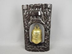 A brass dinner gong on carved and pierced hardwood stand, the brass bell with dragon depiction,