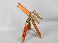 A brass and leather telescopr with sight mounted on a tripod stand