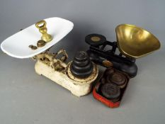 A vintage set of kitchen scales with wights and one other.