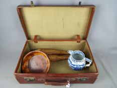 A vintage suitcase, a 19th century blue and white water jug,