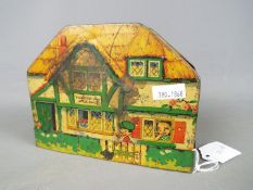 An early 20th century MacFarlane Lang & Co biscuit tin in the form of a cottage,