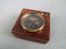A brass compass marked 'Royal Navy' in box.