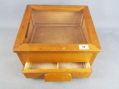 A wooden counter top display cabinet with single drawer,