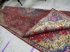 A polychrome Persian Tabarese carpet measuring approximately 328 cm x 232 cm