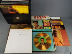 """A collection of 12"""" vinyl records to include Elvis, Rod Stewart, The Carpenters, Motown and similar,"""