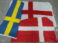 Three flags comprising Denmark, England and Sweden.