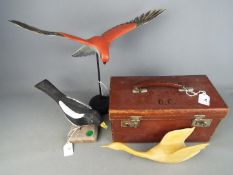 A vintage, leather case of small form and three carved bird figurines.