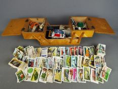 A vintage cantilever sewing box and a collection of tea cards