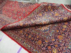 A large red ground Persian Kashan carpet measuring approximately 290 cm x 400 cm
