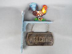 A cast iron, cockerel, welcome sign.