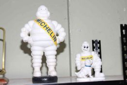 Two cast iron Michelin Men, 40cm and 22cm.