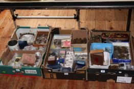 Three boxes of assorted coinage and tokens.