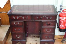 Mahogany eight drawer kneehole desk with central inset cupboard, 76cm by 91.5cm.