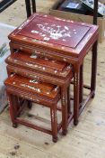 Nest of three Oriental hardwood and mother of pearl inlaid tables, largest 57cm by 44.5cm.