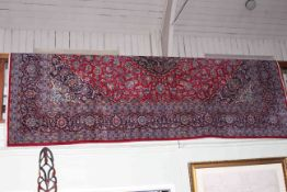 Iranian wool carpet with central medallion and floral design on red ground, 3.60 by 2.50.