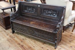 Victorian carved oak box settle, 87cm by 137cm.