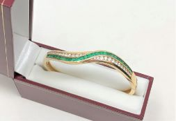 A fine quality 18ct gold emerald and diamond bangle CONDITION REPORT: 26g.