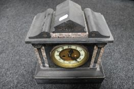An antique black slate and marble mantle clock with brass and enamel dial