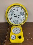 Two yellow enamel wall clocks