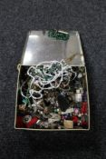 A tin of beaded necklaces, enamel badges,
