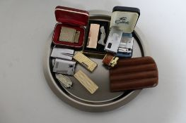 A plated tray containing a collection of assorted gas lighters to include Calibri, Ronson,
