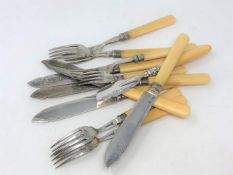 Twelve various pieces of EPNS fish cutlery with silver ferrules.