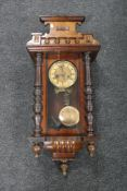 A Victorian stained beech wood wall clock with pendulum