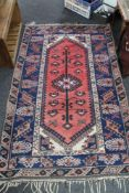 A Persian rug on salmon/blue ground,