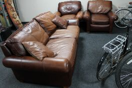 A brown leather three piece lounge suite and brown leather cushions