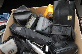 A box of assorted cameras including Kodak, Pentax, Praktica, binoculars,