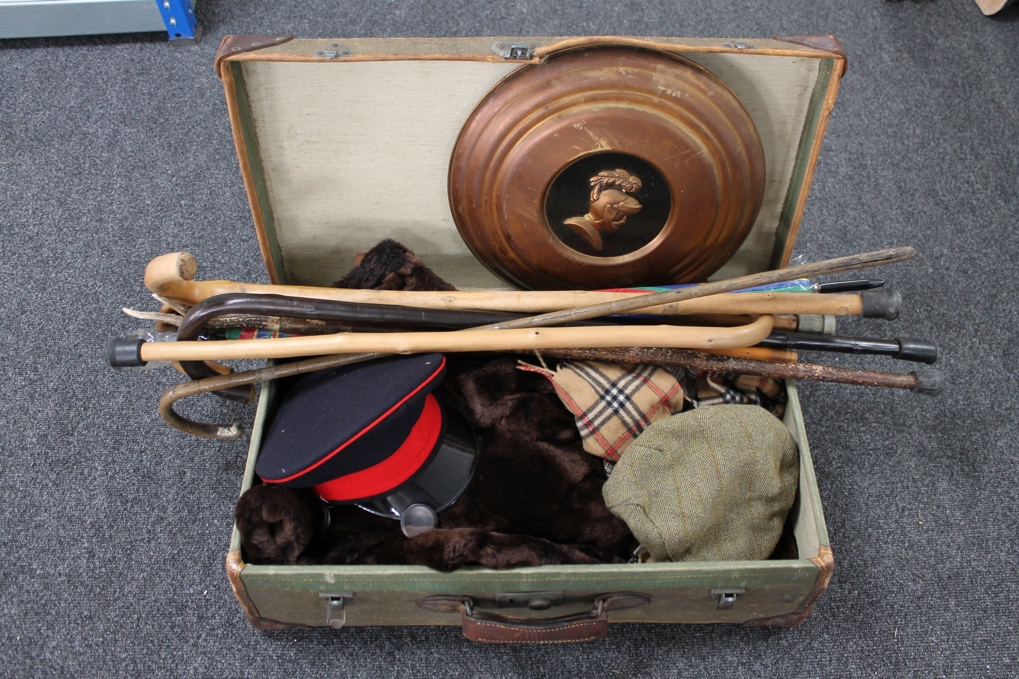 Lot 288 - A vintage suitcase containing various clothing, walking sticks,